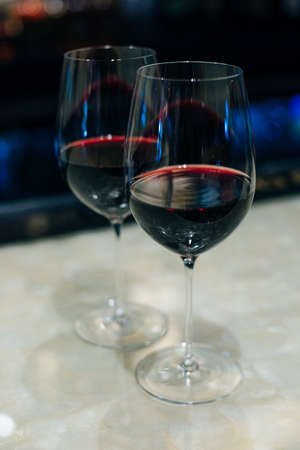 glasses with red wine on bar counter in restaurante.