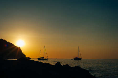 silhouette of a yacht at sunset on the Yanui beach of phuket island, thailand.