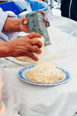 Woman preparing cheese for cook using cheese grater in the kitchen.