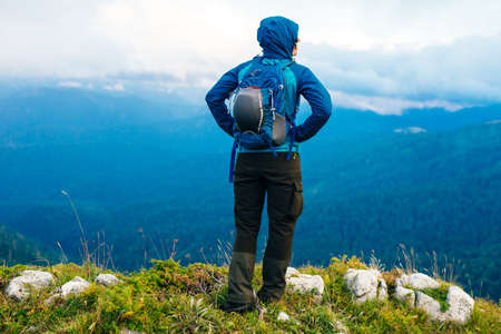 girl in a blue jacket with a hood and a city backpack in the Adygea mountains, Russia. Banco de Imagens