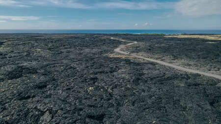 Chain of Craters Road in Hawaii Volcanoes National Park is vivid with blue ocean, waves and black sea cliffs. Cliffs were formed when Mauna Ulu exploded liquid lava. Banco de Imagens