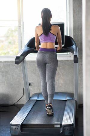 Femme asiatique sur tapis roulant dans la salle de sport Banque d'images