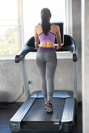 Mujer asiática en cinta en el gimnasio Foto de archivo