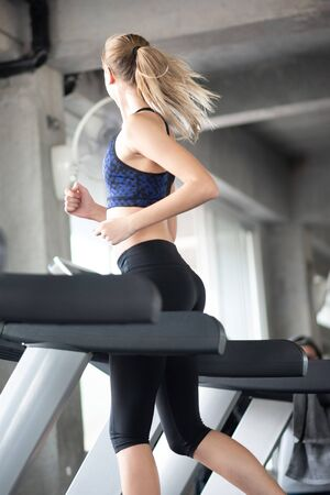 Attractive young sports woman on treadmill in the gym
