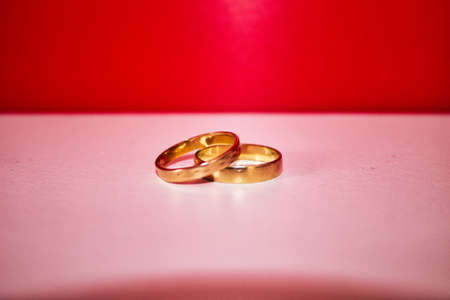 gold wedding rings for valentines day on a red and white background