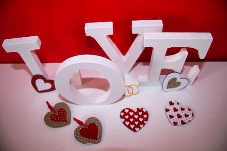 gold wedding rings on a red and white background for valentines day and word love