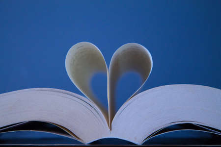 group of books and above one open in the middle with two pages forming a heart for the love of reading on the international day of books on a gray background