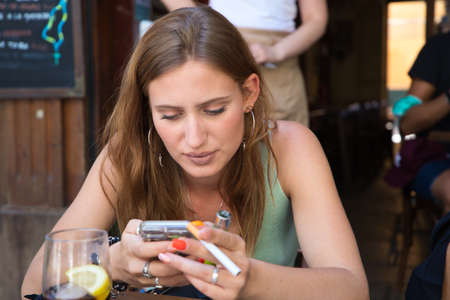 Young and beautiful woman is sitting in a bar. She is looking at her mobile phone and holding a cigarette in her other hand. Concept stop tobacco. Foto de archivo