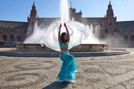 A young and beautiful belly dancer dancing in a square. She is dressed in light blue with a white veil in her hands. World folklore concept from Africa and Asia.