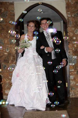 A wedding couple walking in bubbles