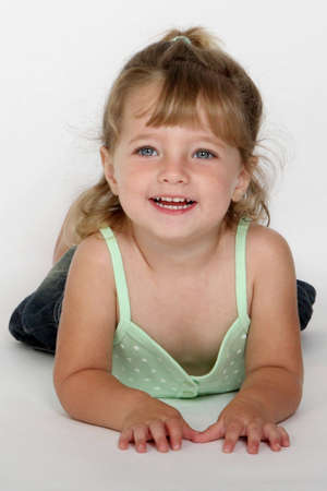 A little girl lying on her stomach smiling photo