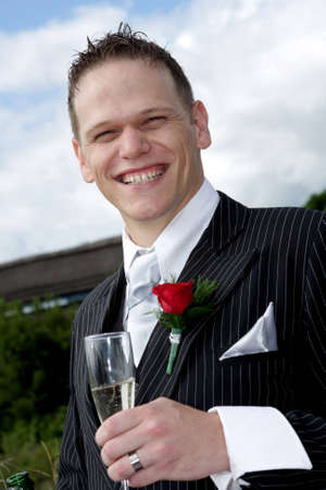 A groom on his wedding day making a toast photo