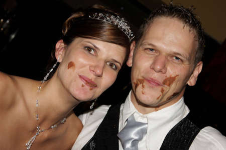 A wedding couple with chocolate on their faces