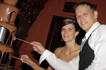 A bride and groom eating from the chocolate fountain photo