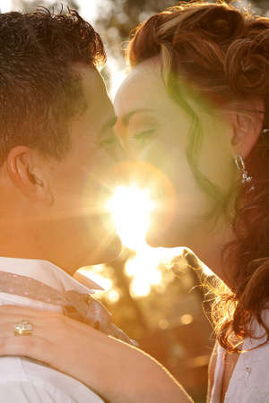 A bride and groom standing in front of the sun