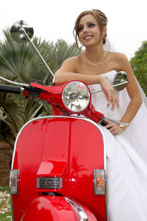 A bride sitting on a red scooter
