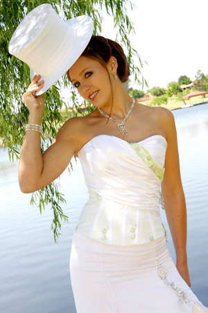 Bride standing outside holding a hat photo