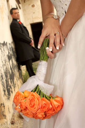A bride holding roses with groom in background photo