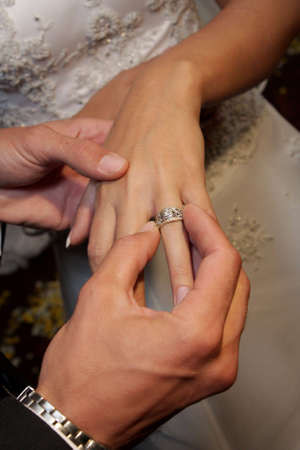 A groom giving his bride a ring Stock Photo