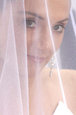 A bride behind her veil before chapel photo