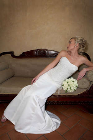 A bride sitting in a couch in her dress Stock Photo