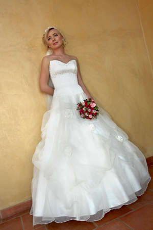 A bride standing against a wall
