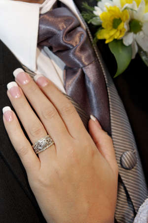 A brides hand on grooms chest