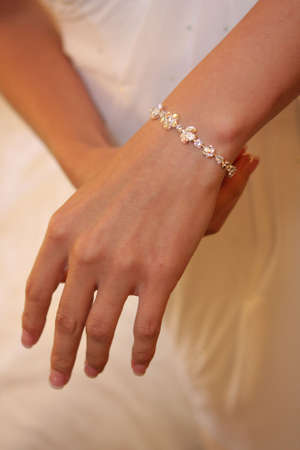 A bride on putting on her bracelet on her arm