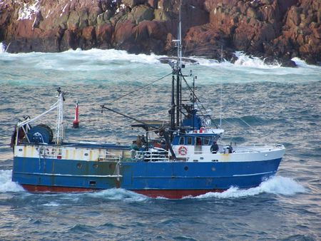 a fishing vessel cuts through ocean water headed to the fishing grounds Stock Photo