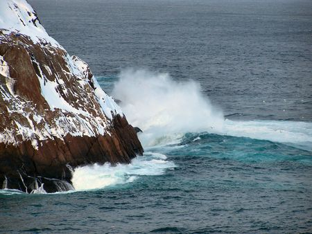 a wave crashes against a rocky shore on a windy day
