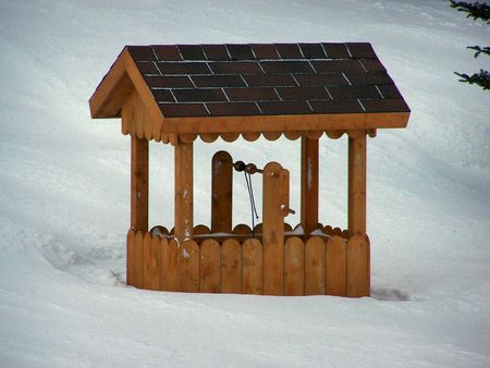 a wishing well buried in snowafter a winter storm