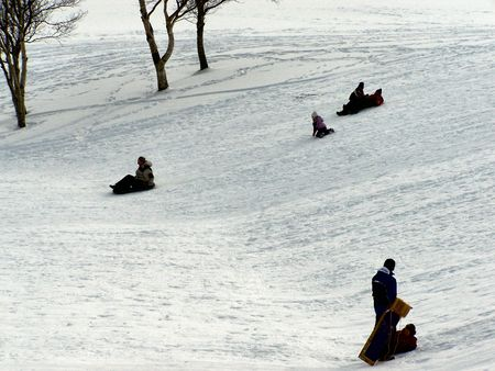 people go sliding on a sunny winter day Stock Photo