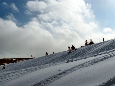 people go sliding on a hill in a local park Stock Photo