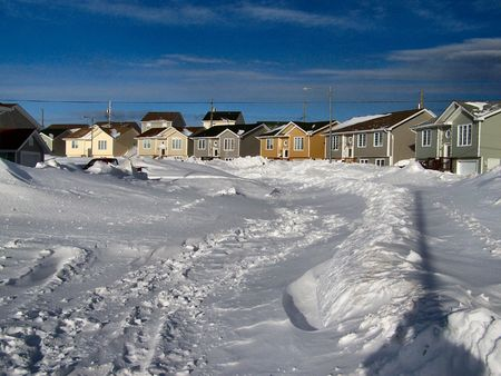 paralyzed: this is the aftermath of a winter blizzard that left the city of st.johns nefoundland canada paralyzed. It would be two days before this particular street would be properly cleared by snow plow.