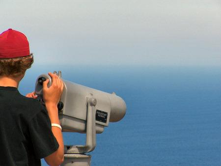 A teen views the wide open ocean through a telescope