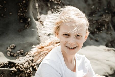 A young girl sitting at a beach cliff with barnicles in the back ground, her blond blonde hair is wind blown and she is looking at the camera