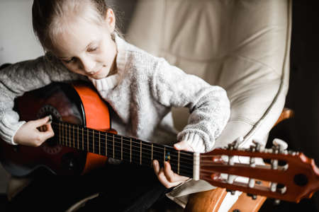 A young blonde caucasion girl sitting by a window practicing her acoustic guitar Stock Photo