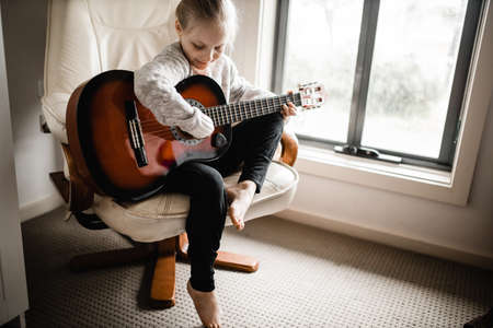 A young blonde caucasion girl sitting by a window practicing her acoustic guitar Reklamní fotografie