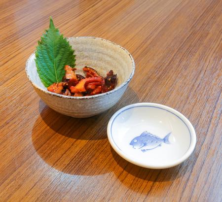 seasoned: Seasoned Baby Octopus  and fish dish on wood table