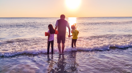 Père et enfants jouant dans la mer au coucher de soleil, arrière-plan flou Banque d'images - 86564170
