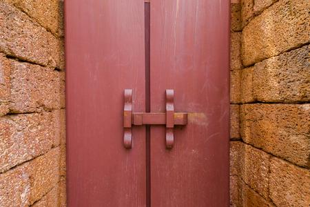 An acient locked door on a wall photo