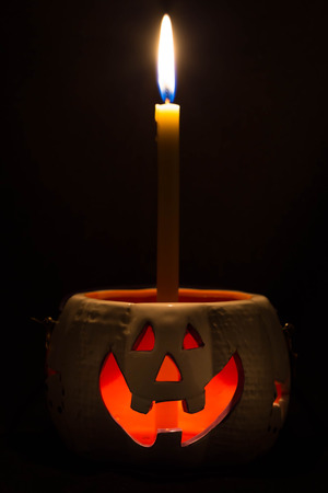 terrific: Jack O Lantern halloween and a candle isolated on dark background