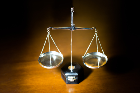 Silver scale of justice on wooden table (Selective focus)