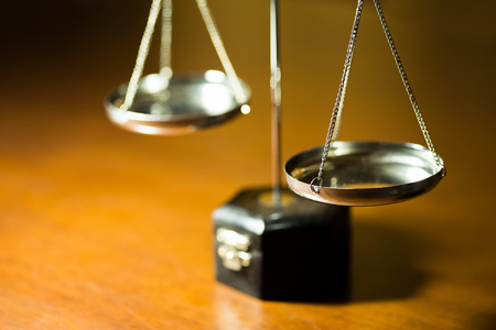 Silver scale of justice on wooden table