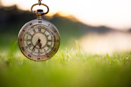 Pocket watch on field in dawn time