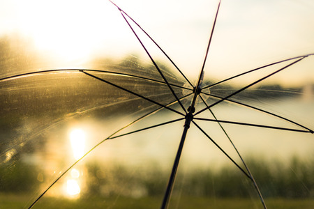 adentro y afuera: Paraguas transparente contra la puesta del sol