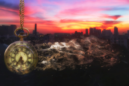 Pocket watch is disintegrating with city scape background at last sunlight (Concept of wasting time)  Stockfoto
