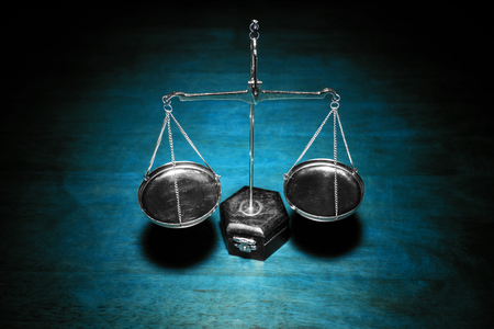 Scale of justice on wooden table (Blue tone)