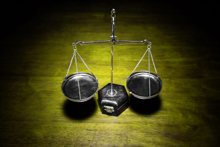 Scale of justice on wooden table (Yellow tone) Stock Photo