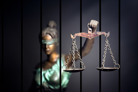 Lady Justice against jail background Banco de Imagens